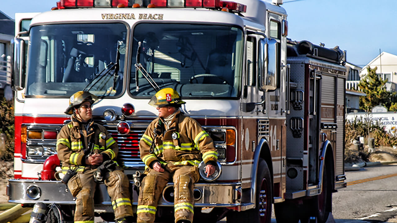 Firefighters in gear sitting on engine bumper.