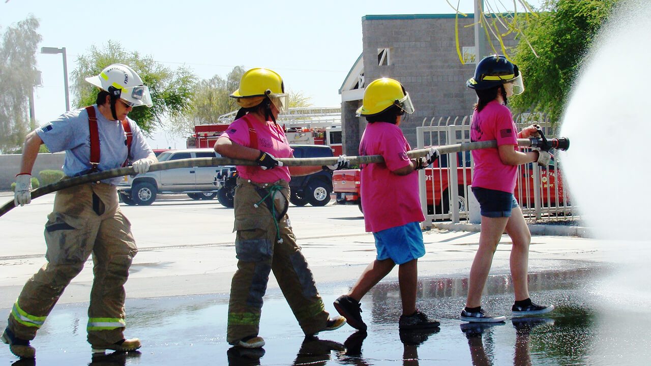 Young girls advancing a fire hose with firefighter helping from behind.