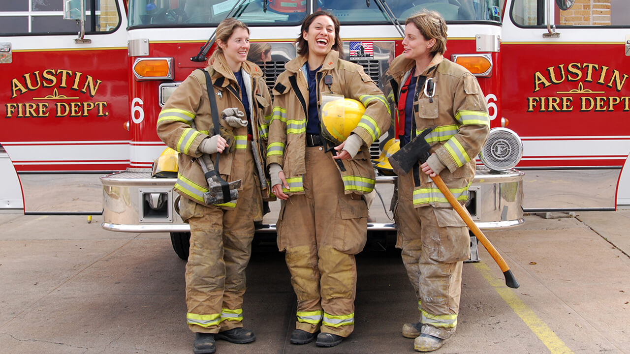 3 women firefighters in front of their rig