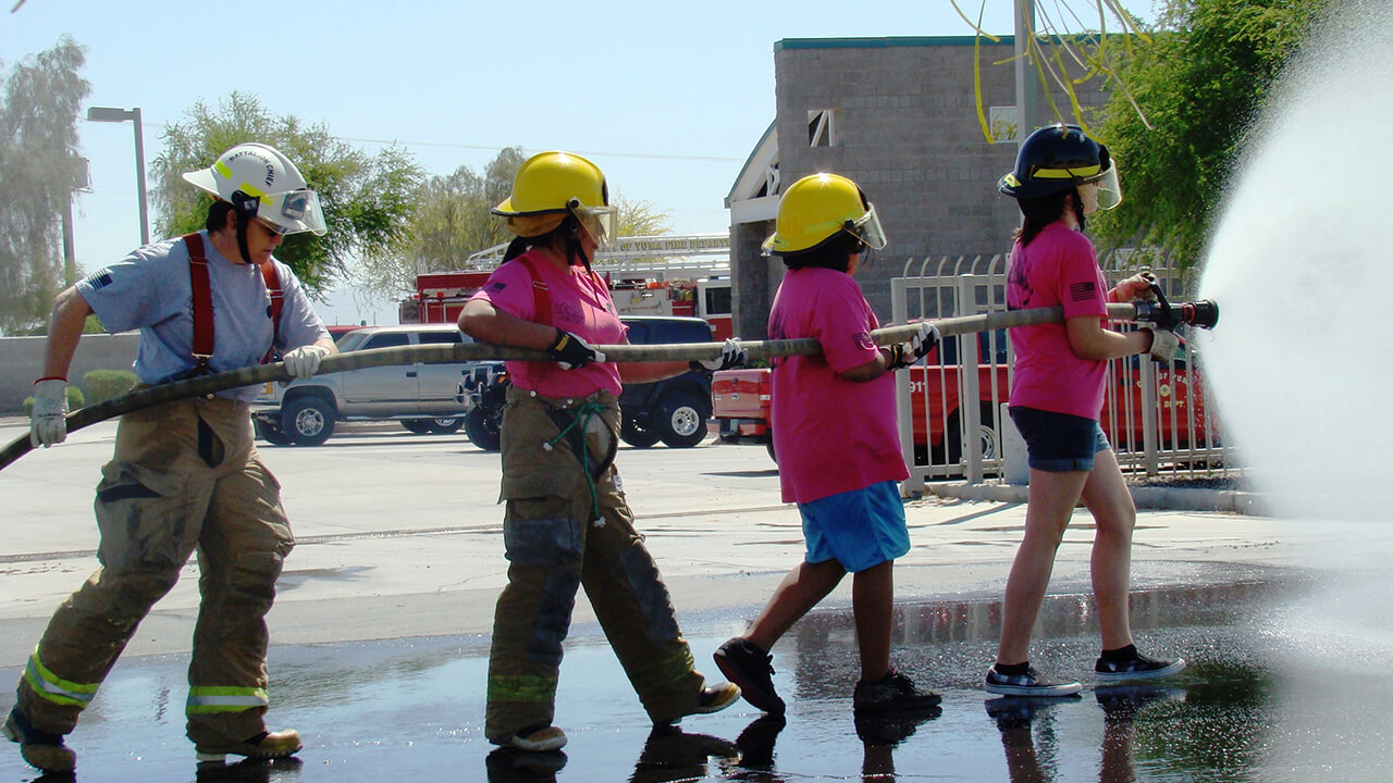 Young girls advancing a hose.