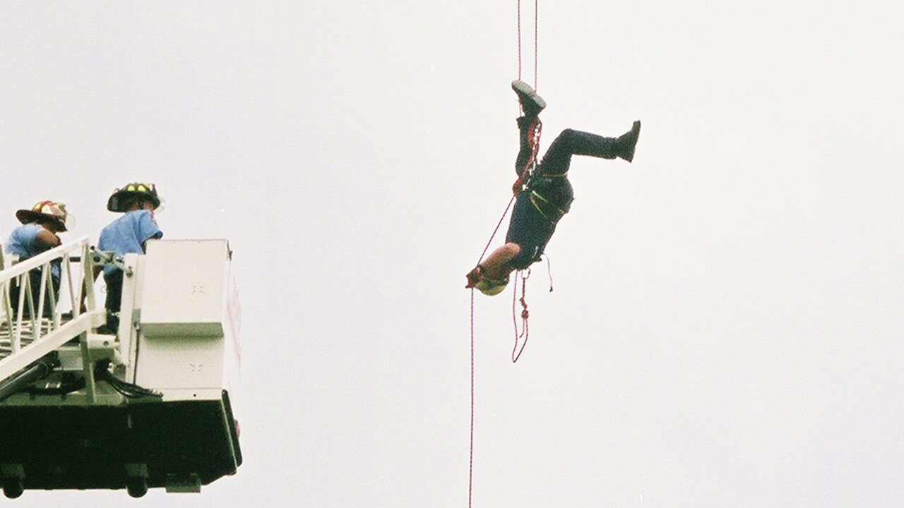 Firefighter dangling in air upside-down.