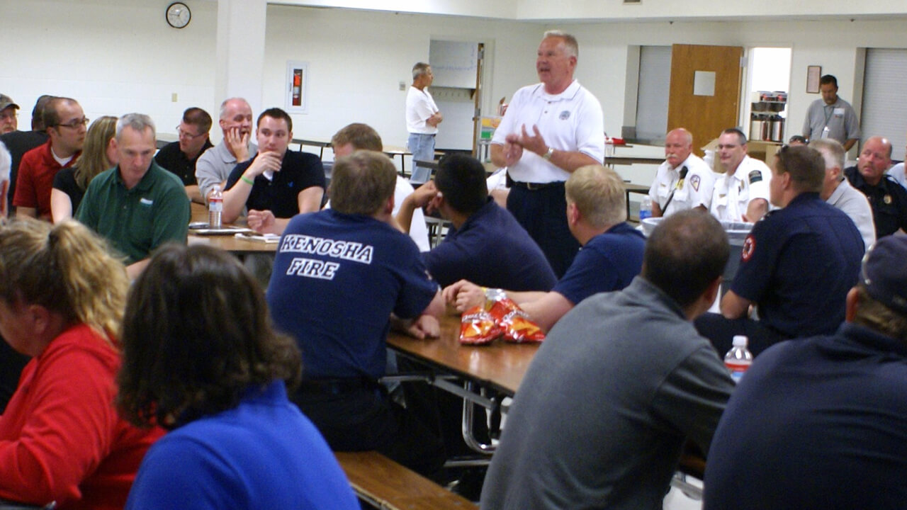 Chief talking to a group of volunteer personnel and recruits