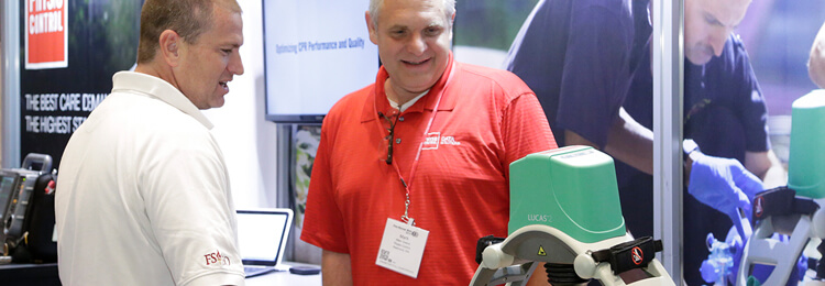 An attendee and exhibitor review a product demo