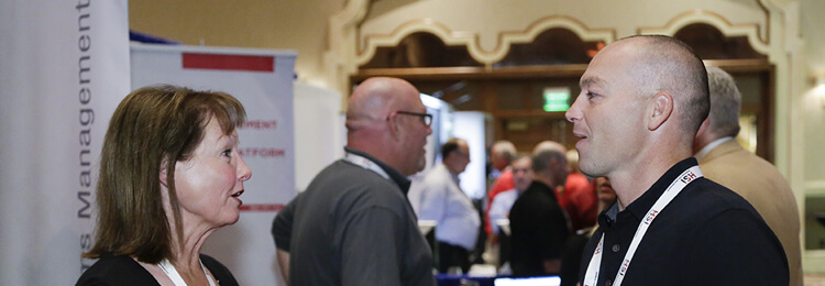 An attendee talks with an exhibitor